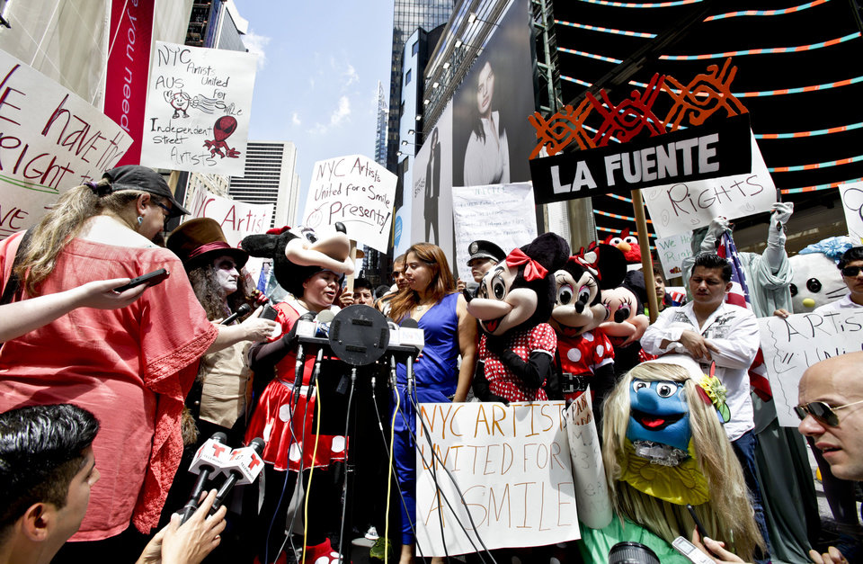 Photo - Giovanna Melendez, 38, fourth from left, who works as a Minnie Mouse costume character, speaks during a press conference, Tuesday, Aug. 19, 2014 at Times Square in New York. Melendez joined the call by NYC Artists United for a Smile for fair treatment and a right to work as costumed characters. Melendez said,