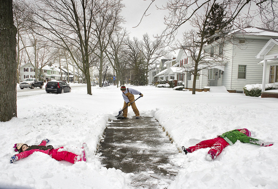 Photo - Jason Smith  clears the sidewalk in front of his home at the 2400 block of Anthony Blvd., in Fort Wayne, Ind., before heading to work Wednesday morning March 6, 2013, as his daughters Kylie Smith, right, 8, and Alexa Smith, 7, make snow angels on their day off from school.  (AP Photo/The Journal Gazette, Swikar Patel)   NEWS-SENTINEL OUT; MANDATORY CREDIT; NO SALES; MAGS OUT