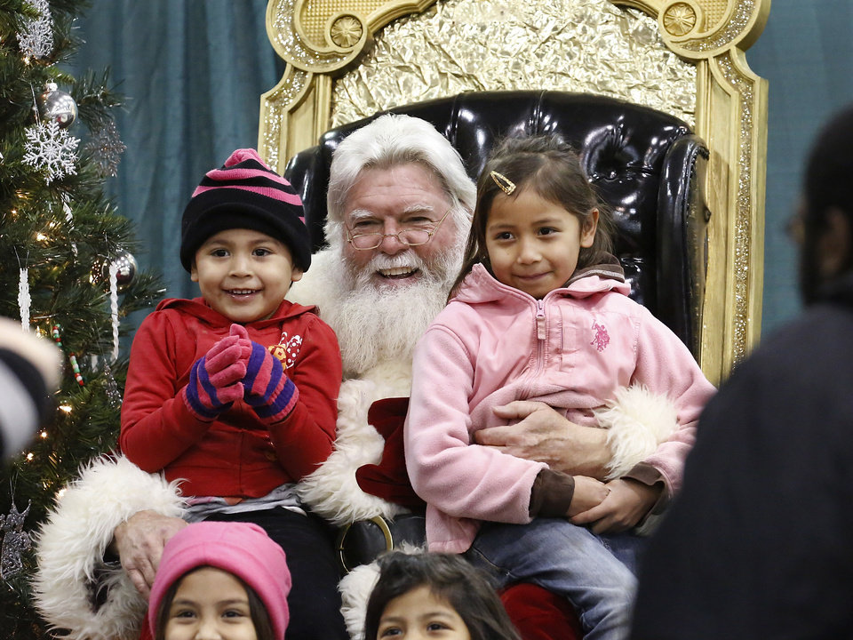 Children pose on Santa's lap for a keepsake photo. Santa is played by Larry Blair, who has played the role of Santa many years, but said this is his first year to be the Santa for guests at the Red Andrews Dinner. Hundreds were served a traditional Christmas meal at the annual Red Andrews Dinner inside the Cox Convention Center on Christmas Day, Dec. 25, 2012. An army of  volunteers showed up despite  snow and ice and hazardous driving conditions. They accompanied each guest through the serving line and carried their trays and seated them at their tables. Other volunteers distributed a small mountain of toys and stuffed animals that were donated for the event.   Photo by Jim Beckel, The Oklahoman <strong>Jim Beckel - THE OKLAHOMAN</strong>