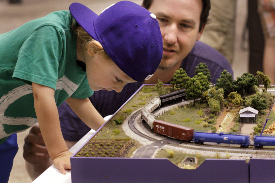 Left: Maverick Beeson, 3, looks at details of a model train display with his dad, Jed Beeson.