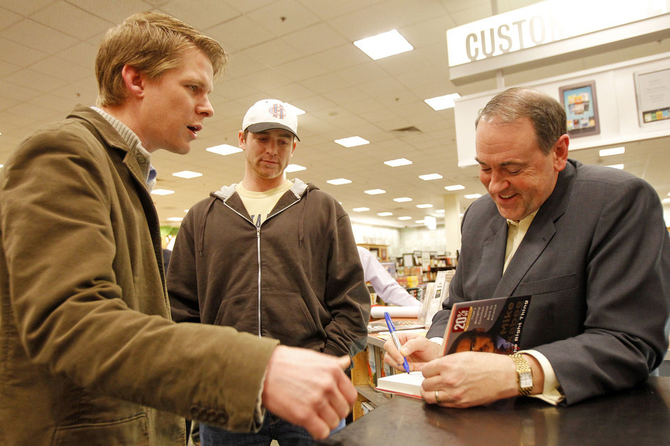 Photo - In this 2011 photo, former Arkansas Gov. Mike Huckabee, right, signs a book for Matt Reisetter, of Cedar Falls, Iowa, as Zach Von Tersch, center, also of Cedar Falls, looks on during a book signing in Waterloo, Iowa. AP PHOTO