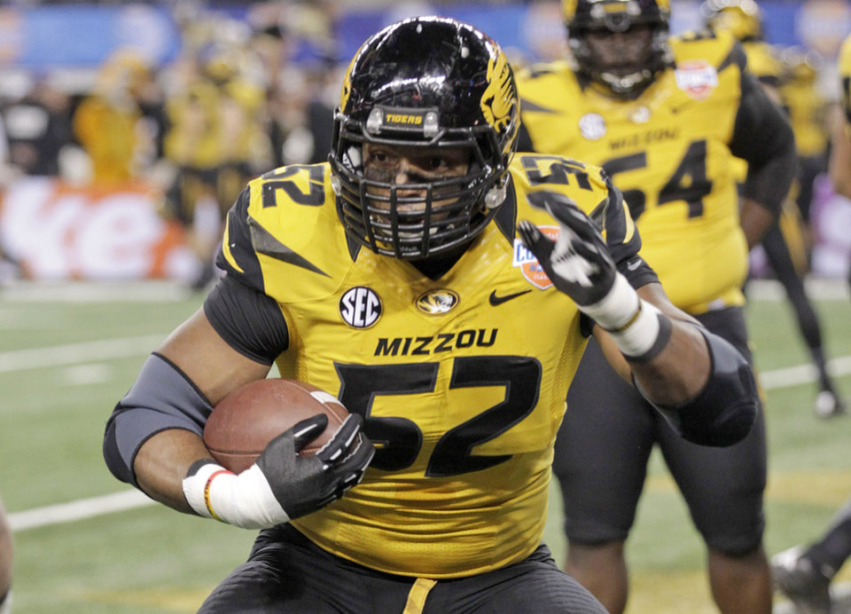 Photo - FILE - In this Jan. 3, 2014 file photo, Missouri defensive lineman Michael Sam (52) warms up before the Cotton Bowl NCAA college football game against Oklahoma State, in Arlington, Texas. Michael Sam hopes his ability is all that matters, not his sexual orientation.  Missouri's All-America defensive end came out to the entire country Sunday night, Feb. 9, 2014, and could become the first openly gay player in America's most popular sport. (AP Photo/Tim Sharp, File)