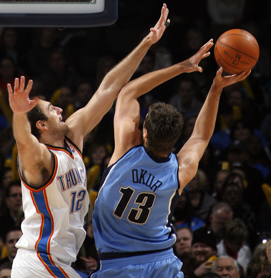 Photo - Nenad Krstic (12) of Oklahoma City tries to block the shot of Mehmet Okur (13) of Utah during the NBA basketball game between the Oklahoma City Thunder and the Utah Jazz at the Ford Center in Oklahoma City, Thursday, December 31, 2009. Photo by Nate Billings, The Oklahoman