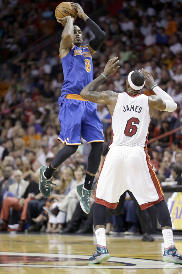 Photo - New York Knicks guard J.R. Smith (8) goes up for a shot against Miami Heat forward LeBron James (6) during the second half of an NBA basketball game, Sunday, April 6, 2014 in Miami. James scored 38 points and Smith made a Knicks-record 10 3-pointers, on an NBA-record 22 attempts, and finished with 32 points as the Heat defeated the Knicks 102-91. (AP Photo/Wilfredo Lee)