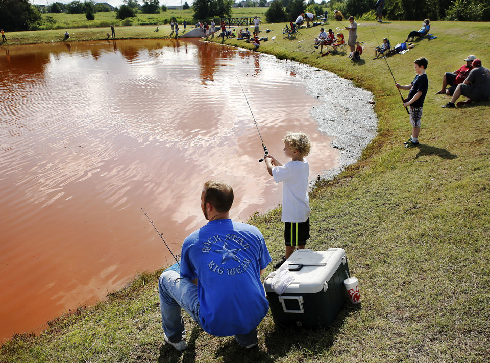 Photo - Corey Hurt and his son, Luke, 5, keep their eyes on their lines while  fishing in the derby. Corey said he and his son are