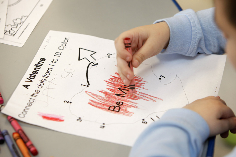 Photo - A child colors a Valentine's Day card during a class for autistic children at Sequoyah Elementary School in Oklahoma City on Thursday.  Photo by Paul Hellstern, The Oklahoman