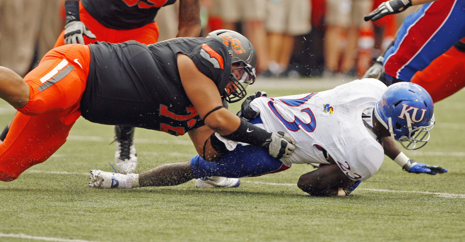 Photo - Oklahoma State's Christian Littlehead (72) tackles Kansas' Tony Pierson (23) for a loss during a college football game between the Oklahoma State University Cowboys (OSU) and the University of Kansas Jayhawks (KU) at Boone Pickens Stadium in Stillwater, Okla., Saturday, Oct. 8, 2011 Photo by Steve Sisney, The Oklahoman