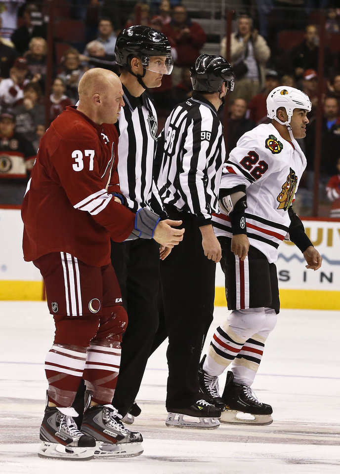 Photo - Phoenix Coyotes' Raffi Torres (37) and Jamal Mayers (22) are taken to the penalty box by linesmen John Grandt (98) and Shane Heyer after fighting during the first period in an NHL hockey game Thursday, Feb. 7, 2013, in Glendale, Ariz.(AP Photo/Ross D. Franklin)