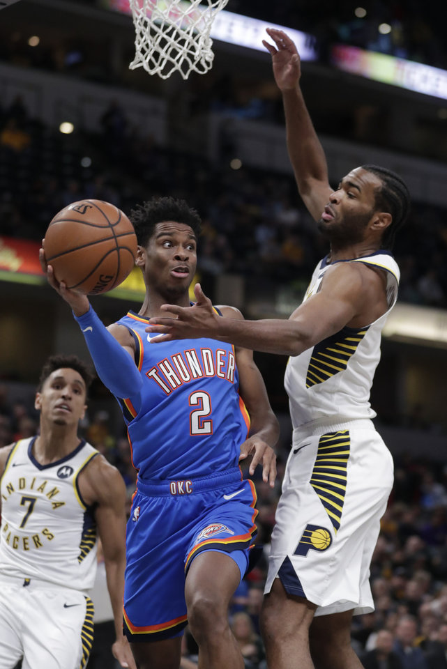 Photo - Oklahoma City Thunder guard Shai Gilgeous-Alexander (2) makes a pass around Indiana Pacers forward T.J. Warren during the first half of an NBA basketball game in Indianapolis, Tuesday, Nov. 12, 2019. (AP Photo/Michael Conroy)