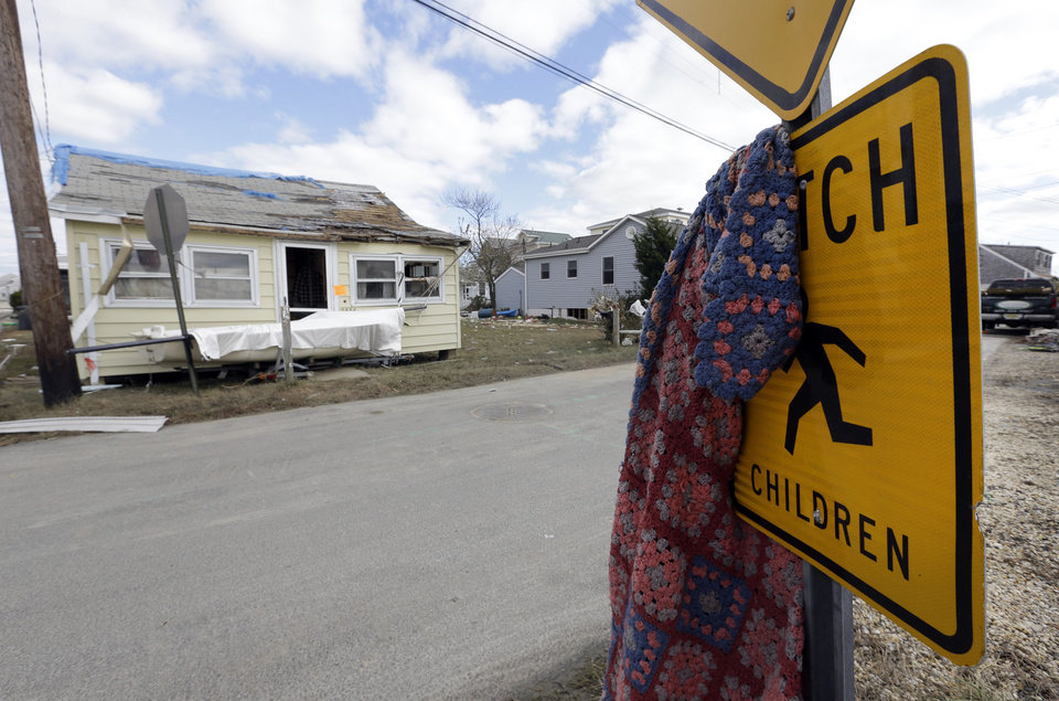 Photo -   A quilt hangs from a street sign across the street from a house that was damaged by surge from Superstorm Sandy on Cedar Bonnet Island, N.J., Saturday, Nov. 3, 2012. (AP Photo/Patrick Semansky)