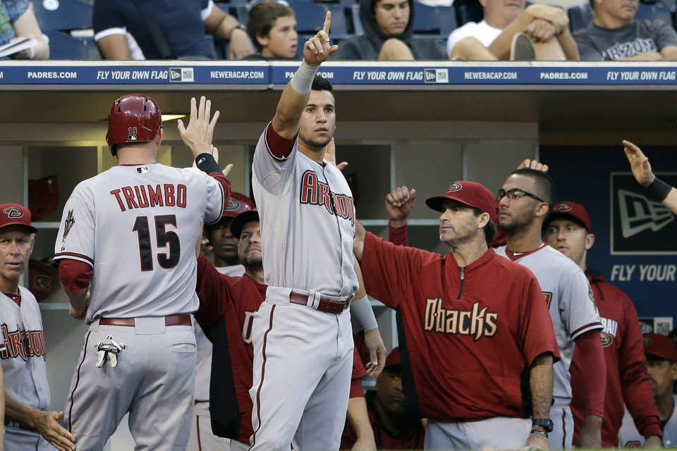 Photo - Arizona Diamondbacks' David Peralta, center, points to teammate Miguel Montero on first base after Montero hit an RBI-single, driving home Mark Trumbo (15) while playing the San Diego Padres during the third inning of a baseball game Thursday, Sept. 4, 2014, in San Diego. (AP Photo/Gregory Bull)