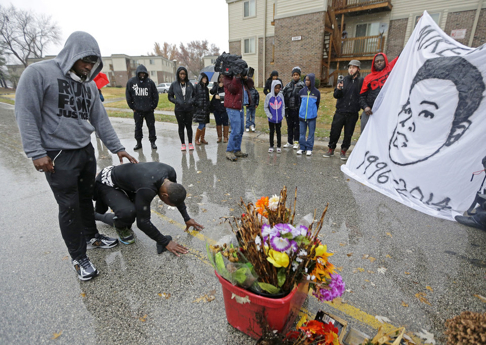 Photo - Ray Mills, left, and Londrelle Hall pause before a memorial in the middle of a street Sunday, Nov. 23, 2014, more than three months after a black 18-year-old was shot and killed there by a white policeman in Ferguson, Mo. The two men spent 20 days running from their home in Atlanta in an effort to raise awareness of the shooting. Ferguson and the St. Louis region are on edge in anticipation of the announcement by a grand jury whether to criminally charge Officer Darren Wilson in the killing of Michael Brown. (AP Photo/Charlie Riedel)