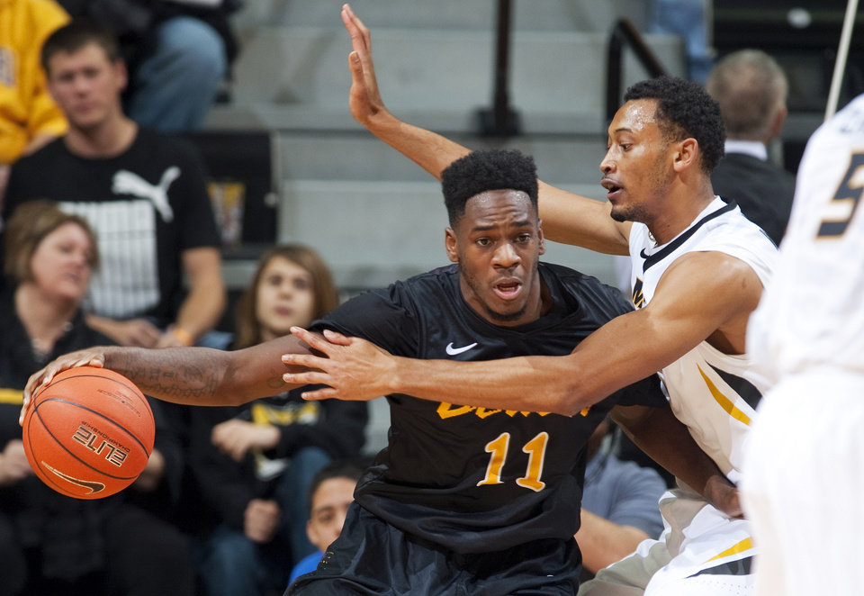 Photo - Long Beach State's David Samuels, left, pushes past Missouri's Johnathan Williams III, right, as he drives to the basket during the first half of an NCAA college basketball game Saturday, Jan. 4, 2014, in Columbia, Mo. (AP Photo/L.G. Patterson)