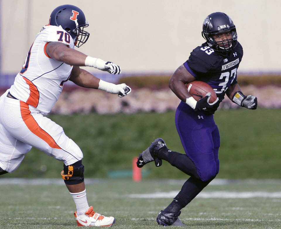 Photo -   Northwestern linebacker David Nwabuisi (33) runs an interception ahead of Illinois offensive line Corey Lewis (70) during the first half of an NCAA college football game in Evanston, Ill., Saturday, Nov. 24, 2012. (AP Photo/Nam Y. Huh)