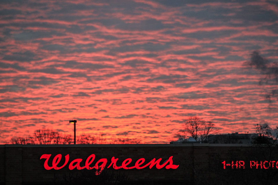 Photo - FILE - In this Friday, Feb. 1, 2013, file photo, the sun rises behind a Walgreens drug store in Omaha, Neb. Walgreens reports quarterly earnings on Tuesday, Oct. 1, 2013. (AP Photo/Nati Harnik, File)