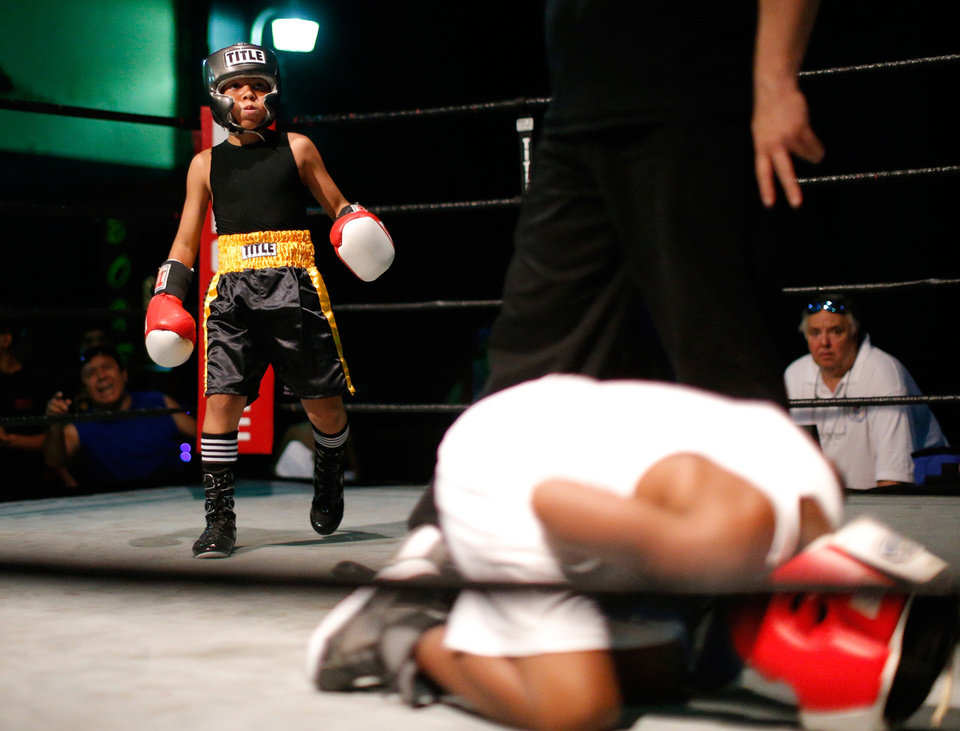 Photo -  Nine-year-old Chris Barba, of Edmond, watches, after knocking down Roderick Tisdale, 10, of Pawhuska, during the pair's first fight at The Underground Arena in Oklahoma City, Saturday, June 15, 2013. Photo by Bryan Terry, The Oklahoman