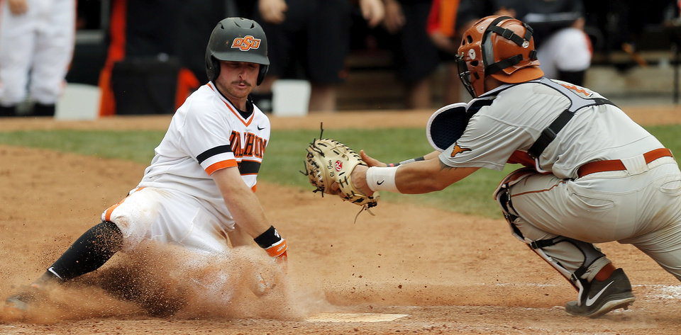 Photo - OSU's Saulyer Saxon (3) slides home to score past UT catcher Tres Barrera (1) for the go-ahead run in the eighth inning during a college baseball game between Texas and Oklahoma State in the Big 12 baseball tournament at the Chickasaw Bricktown Ballpark in Oklahoma City,  Saturday, May 24, 2014. OSU won 3-1 to force an elimination game. Photo by Nate Billings, The Oklahoman