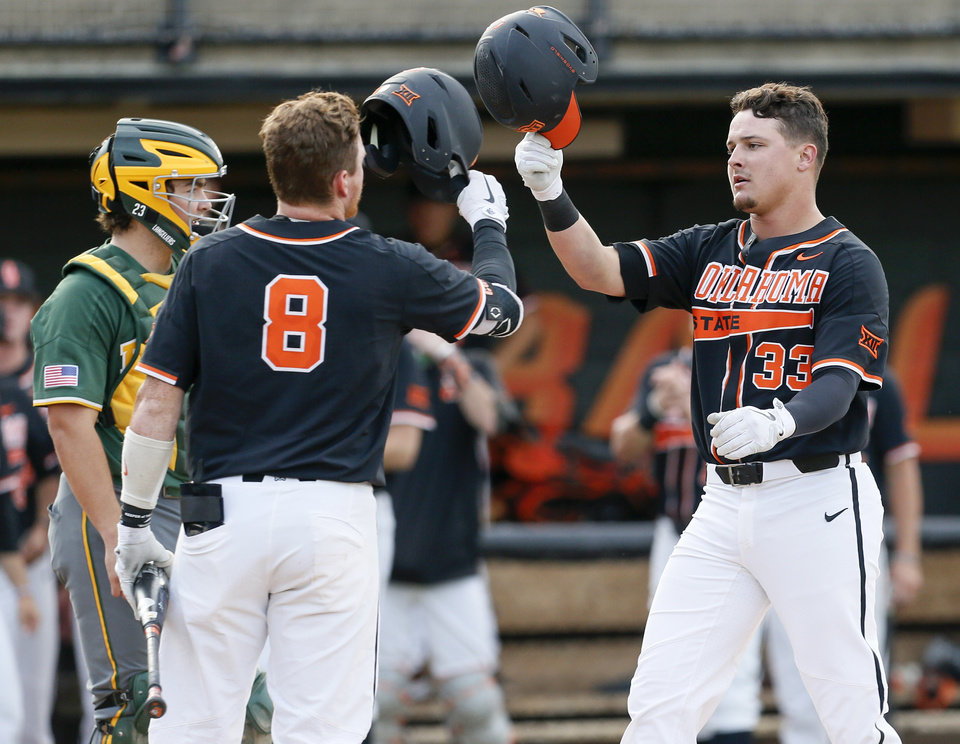 Photo - OSU's Trevor Boone (33) taps helmets with Bryce Carter (8) in front of Baylor catcher Shea Langeliers (23) after Boone hit a home run in the second inning during a college baseball game between Baylor and Oklahoma State in the last regular-season series at Allie P. Reynolds Stadium in Stillwater, Okla., Friday, May 17, 2019. [Nate Billings/The Oklahoman]