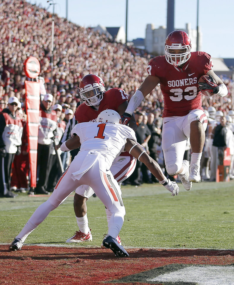Photo - Oklahoma's Trey Millard (33) leaps into the endzone for a touchdown during the Bedlam college football game between the University of Oklahoma Sooners (OU) and the Oklahoma State University Cowboys (OSU) at Gaylord Family-Oklahoma Memorial Stadium in Norman, Okla., Saturday, Nov. 24, 2012. Photo by, Sarah Phipps The Oklahoman