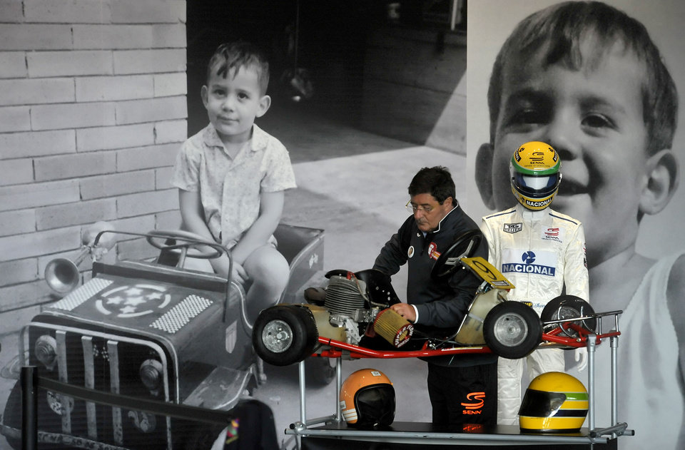 Photo - A man is framed by pictures of late F1 driver Ayrton Senna when he was a boy as he checks a go-kart on display at the Imola track, Italy, Wednesday, April 30, 2014. Fans and family members are gathering this week to pay their respects to former Formula One drivers Ayrton Senna and Roland Ratzenberger on the 20th anniversary of their deaths. F1 drivers' chaplain Sergio Mantovani celebrated a memorial mass Wednesday in a packed room beside pit lane at the Enzo and Dino Ferrari track that once hosted the San Marino Grand Prix. (AP Photo/Marco Vasini)