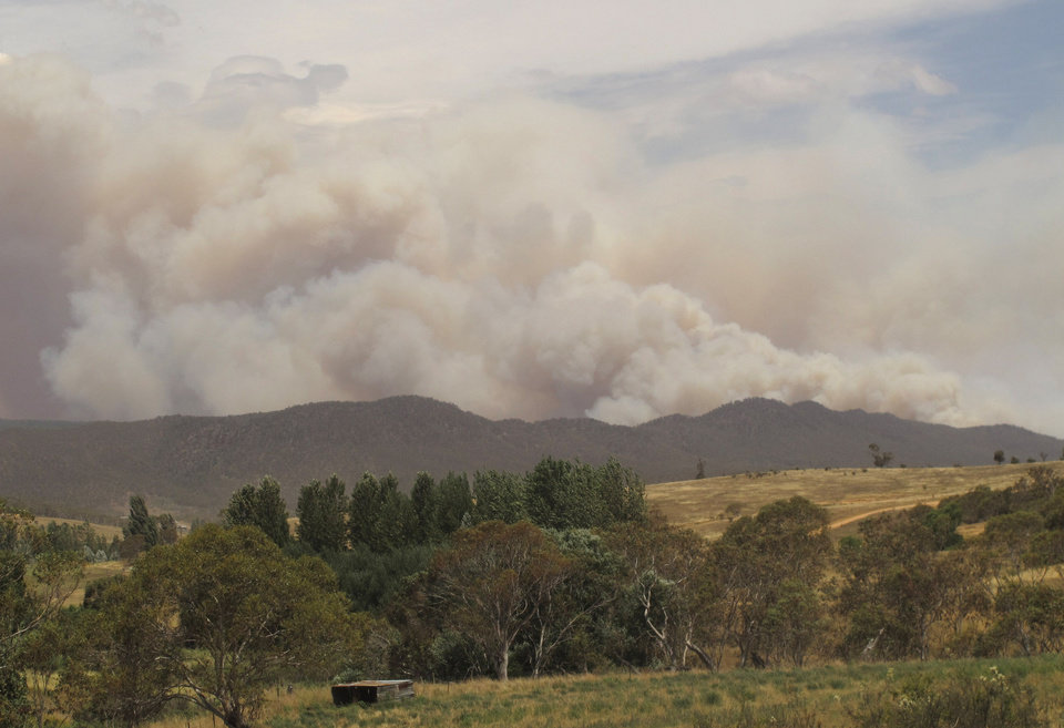 Wildfire smoke rises from hills near the village of Numeralla in New South Wales state on Tuesday, Jan. 8, 2013. Wildfires raged across much of southeast Australia. (AP Photo/Rod McGuirk)