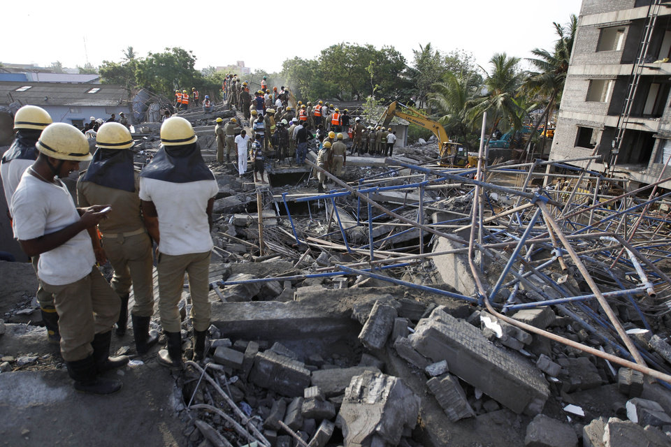 Photo - A rescuer, left checks his mobile phone as they search amid the rubble of a building that collapsed late Saturday during monsoon rains on the outskirts of Chennai, India, Sunday, June 29, 2014. Police said dozens of workers have been pulled out so far and the search is continuing. (AP Photo/Arun Sankar K)