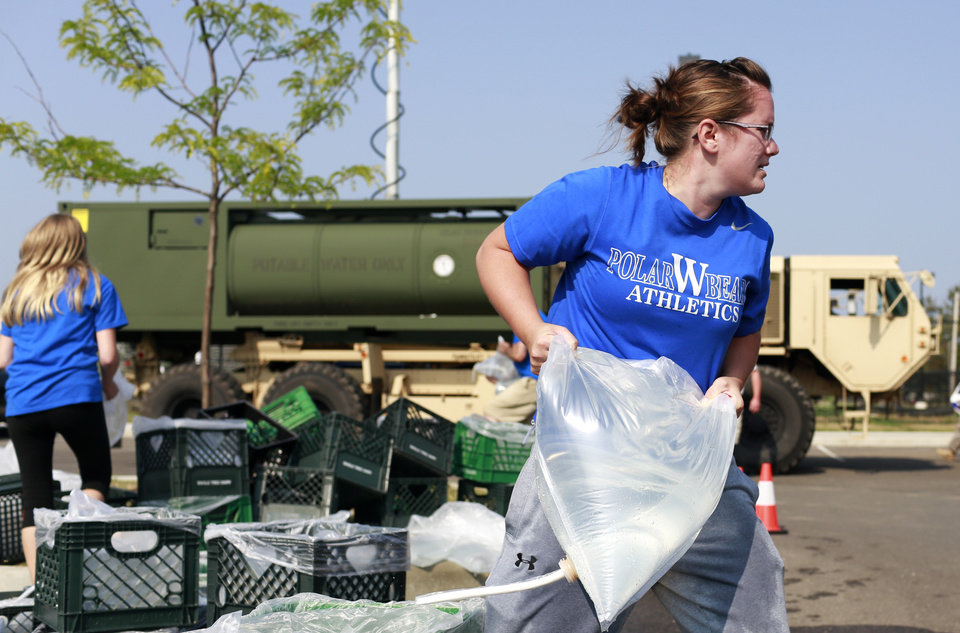 Photo - Megan Anllo, a volleyball coach at at Woodward High School, carries a bag of water to a nearby car, Sunday, Aug. 3, 2014, in Toledo, Ohio. More tests are needed to ensure that toxins are out of Toledo's water supply, the mayor said Sunday, instructing the 400,000 people in the region to avoid drinking tap water for a second day. Toledo officials issued the warning early Saturday after tests at one treatment plant showed two sample readings for microsystin above the standard for consumption, possibly because of algae on Lake Erie. (AP Photo/Haraz N. Ghanbari)