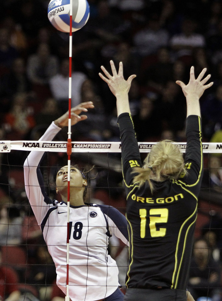Penn State's Deja McClendon (18) flicks this ball around the net antenna and over the outstretched arms of Oregon's Micha Hancock (12) during the national semifinals of the NCAA college women's volleyball tournament semifinal in Louisville, Ky., Thursday, Dec. 13, 2012.  (AP Photo/Garry Jones)