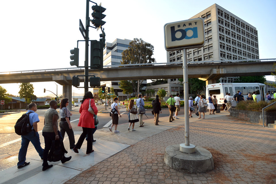 Photo - Commuters work their way down California Boulevard to a line of buses waiting to take them to San Francisco on the second day of the BART strike in Walnut Creek, Calif., on Tuesday, July 2, 2013.  (AP Photo/The Contra Costa Times, Dan Rosenstrauch)