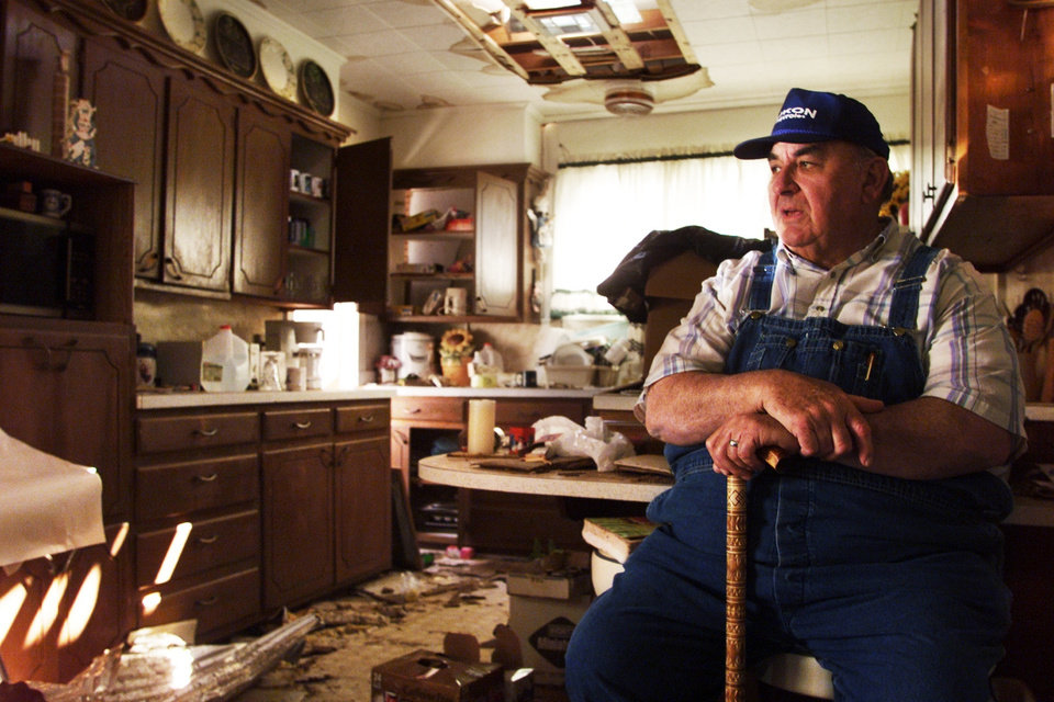 Tornado victims, damage: Gilbert Forrest, pastor of Mulhall Christian Church, sits in the kitchen of the parsonage.  Forrest, who had hip replacement surgery in March, found refuge in a hallway as a tornado removed his roof and blew a piece of steel roofing within a few feet of him.