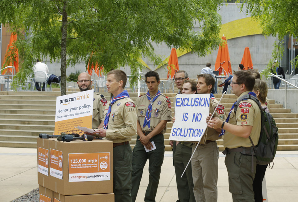 Photo - Jesse Pacem, second from left, chapter leader Chief Seattle Scouts for Equality, speaks in front of a group of Boy Scouts and scout leaders, Wednesday, May 21, 2014, outside the headquarters of Amazon.com in Seattle. The group delivered a petition bearing more than 125,000 signatures, urging Amazon to stop donating money to the Boy Scouts due to the organization's policy of excluding openly gay adults from leadership positions, despite recently accepting gay youth as scouts. (AP Photo/Ted S. Warren)