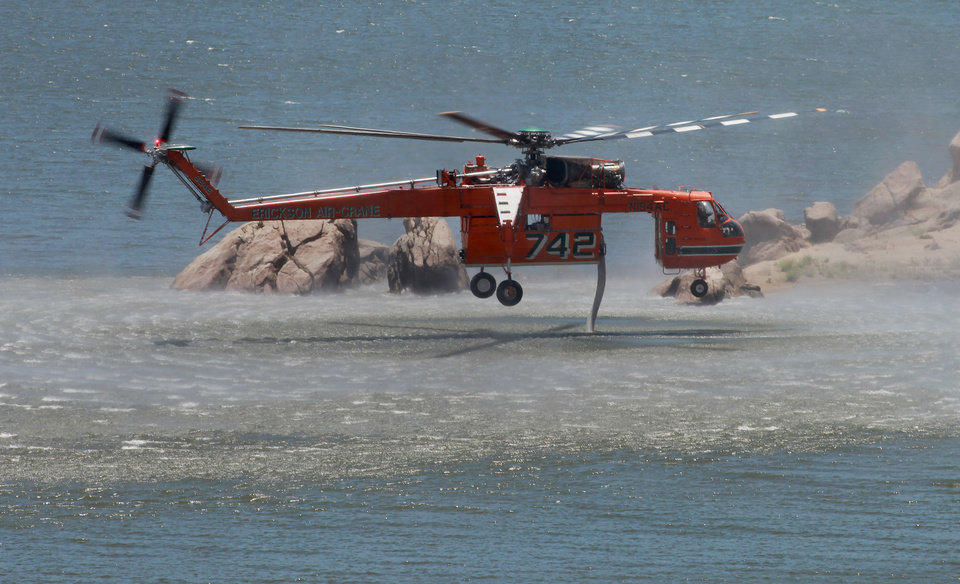 Photo - An Erickson Air-Crane loads up from Isabella Lake Sunday, June 15, 2014 before making another water drop on the Shirley Fire  west of Wofford Heights, Calif. The Kern County Sheriff's Office has called for the evacuation of about 500 homes in the Wofford Heights area.  (AP photo/The Bakersfield Californian, Casey Christie)