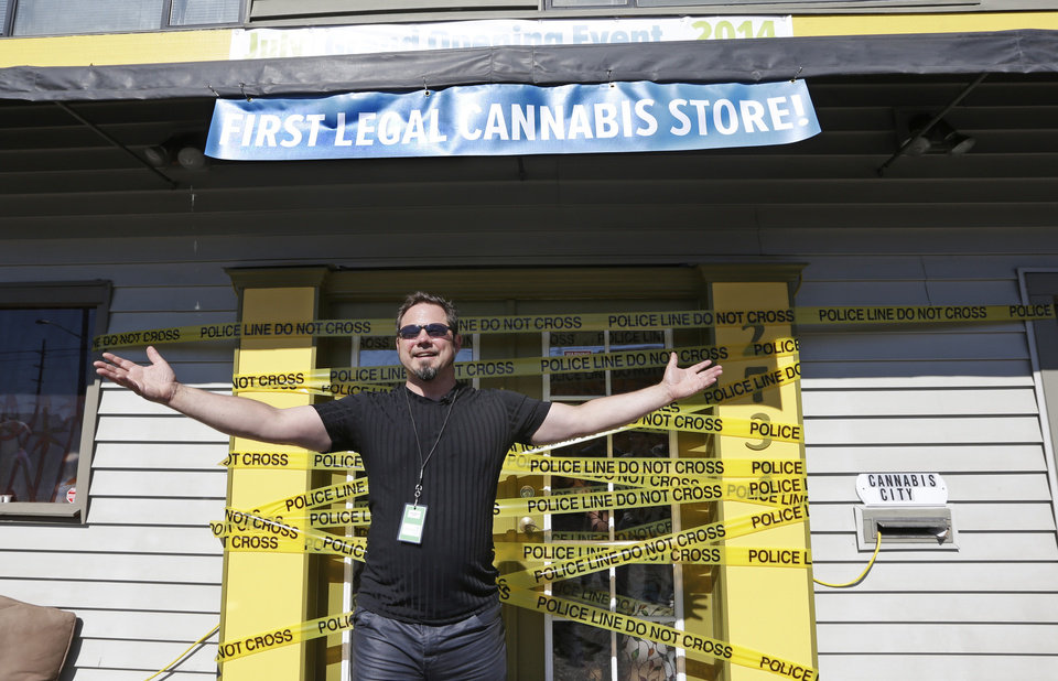 Photo - Cannabis City owner James Lathrop turns around to mug for a photo after putting up lines of police tape on the front of his shop to cut later for the opening on the first day that sales of recreational pot is legal Tuesday, July 8, 2014, in Seattle.  Washington on Tuesday became the second state to allow people to buy marijuana legally in the U.S. without a doctor's note as eager customers who lined up outside stores made their purchases and savored the moment. (AP Photo/Elaine Thompson)