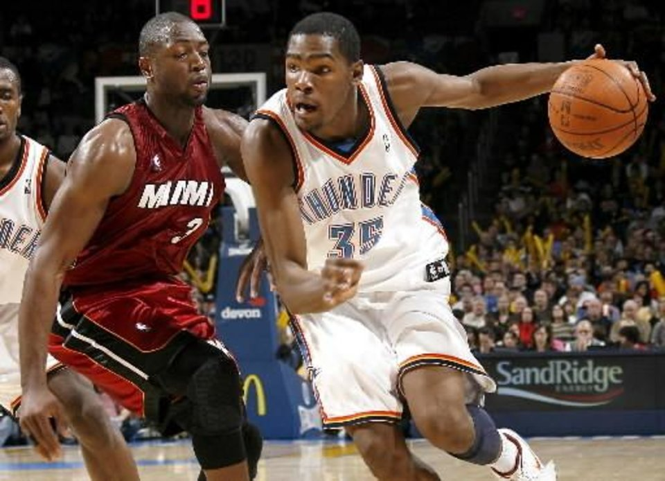 Photo - Oklahoma City's  Kevin  Durant goes around Miami's Dwyane Wade during the NBA basketball game between the Oklahoma City Thunder and the Miami Heat at the Ford Center in Oklahoma City, Saturday, January 16, 2010. Photo by Bryan Terry