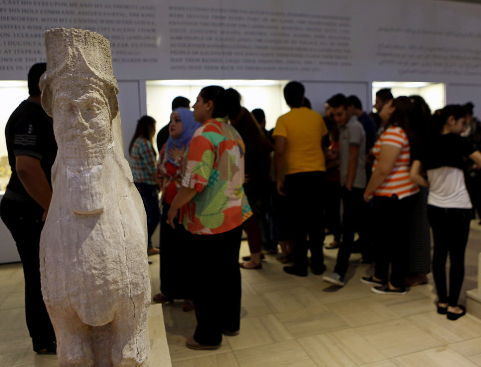 Photo - People invited for a ceremony inaugurating two renovated halls, visit the Iraqi National Museum, in Baghdad, Iraq, Thursday, Aug 21, 2014. Two renovated halls adorned mainly with rare life-size stone statues were inaugurated at the Iraqi National Museum on Thursday geared toward honoring the 5,000 year legacy of the ancient city of Hatra. (AP Photo/Hadi Mizban)