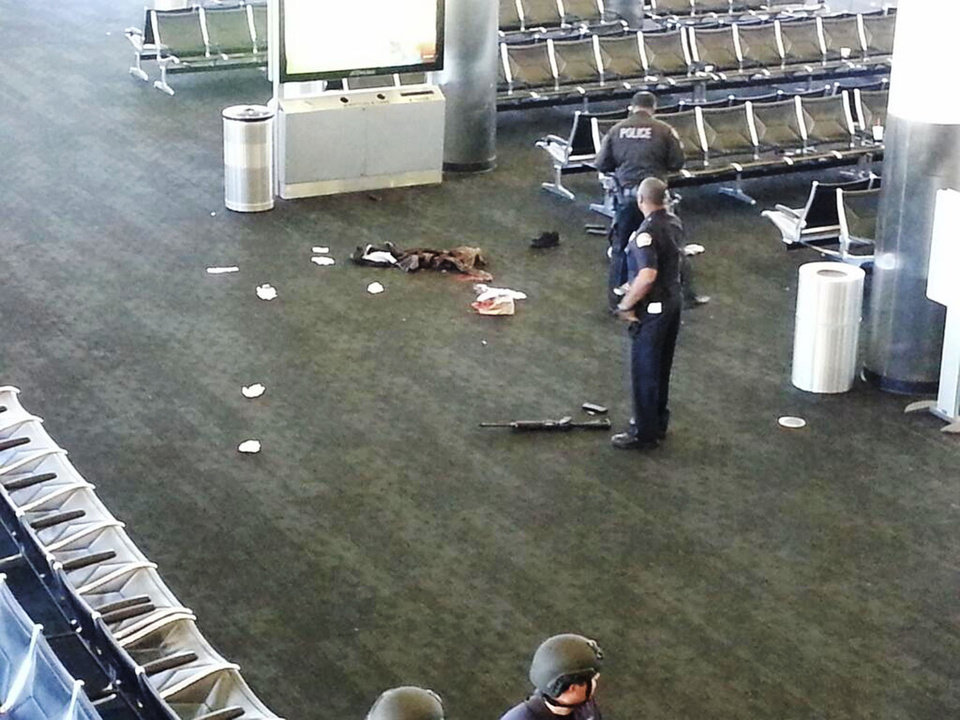 In this photo provided to the AP, which has been authenticated based on its contents and other AP reporting, police officers stand near an unidentified weapon in Terminal 3 of the Los Angeles International Airport on Friday, Nov. 1, 2013. Officials said a gunman who opened fire in the terminal was wounded in a shootout with police and taken into custody. (AP Photo)