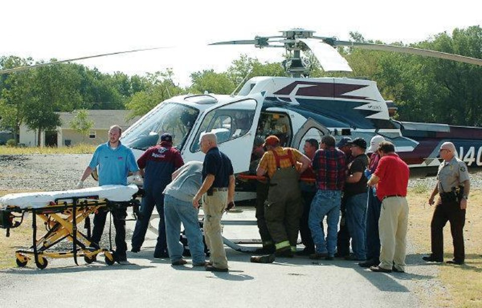 Photo - Emergency responders load an injured teen into an awaiting air ambulance at Zaloudek Grain Company in Kremlin, Okla. Thursday, August 4, 2011. Tyler Zander and Bryce Gannon, both 17, were extricated from a grain auger and taken by Eagle-Med helicopter to OU Medical Center in Oklahoma City with leg injuries. Photo by Cass Rains/Enid News & Eagle ORG XMIT: KOD