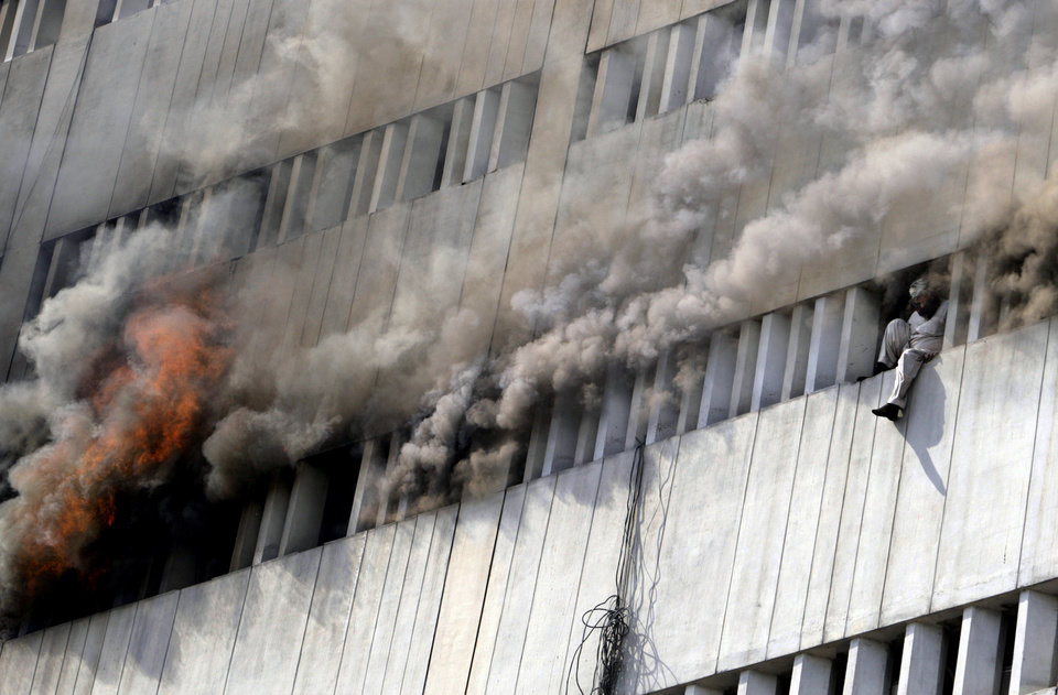 Photo - A Pakistani man moments before jumping from the fifth floor of a building that caught on fire in Lahore, Pakistan, Thursday, May 9, 2013. The 13-storey government building caught fire and quickly intensified spreading to three floors of the tall building. (AP Photo/K.M. Chaudary)