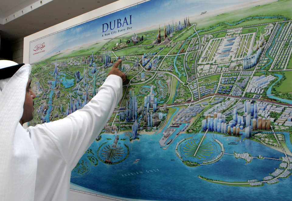 Photo -   FILE - In this file photo dated Tuesday, Oct. 7, 2008, An Emirati man examines a graphic city map of Dubai, depicting new real estate developments, during an exhibition entitled Cityscape exhibition in Dubai, United Arab Emirates. It suddenly seems like Dubai is rediscovering its old habits. That means breathless hype is now back in vogue. Construction plans are again peppered with superlatives. (AP Photo/Kamran Jebreili, File)