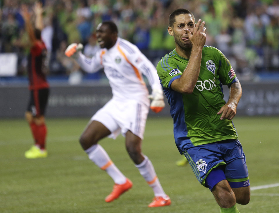 Photo - Seattle Sounders' Clint Dempsey, right, makes a face as Portland Timbers goalkeeper Donovan Ricketts protests at left, after Dempsey scored a goal in the second half of an MLS soccer match, Sunday, July 13, 2014, in Seattle. The Sounders won 2-0. (AP Photo/Ted S. Warren)