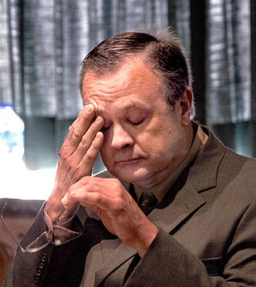 Photo - Roger Q. Melson Jr. wipes sweat from his face during his sentencing hearing for embezzlement on Nov. 9, 2010.  JIM BECKEL