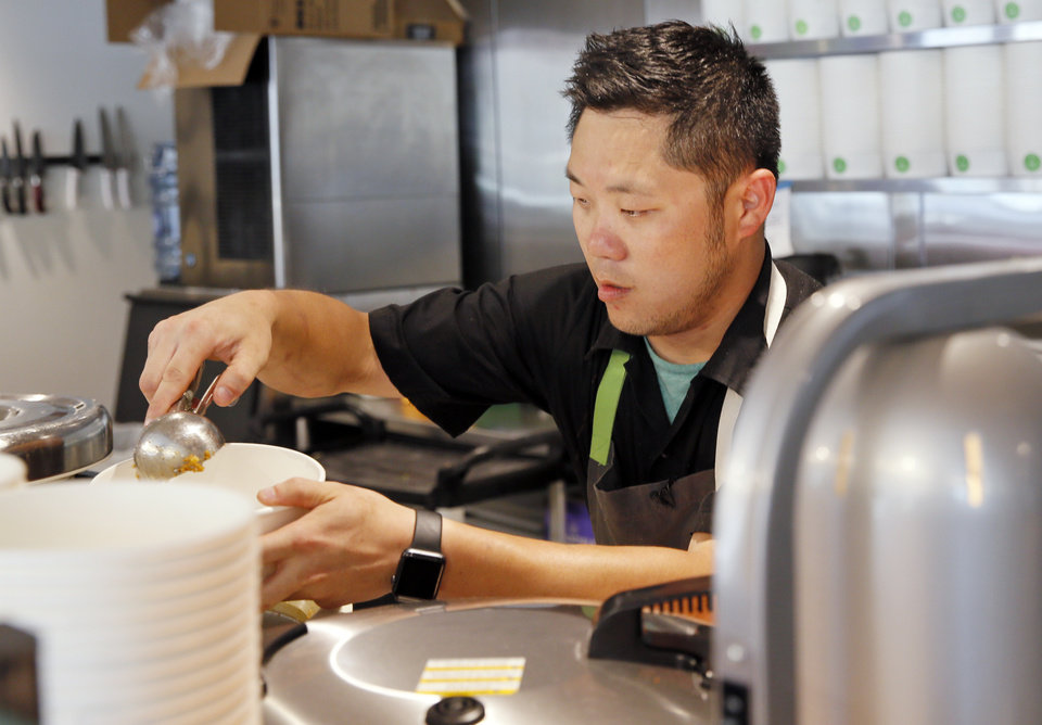 Photo -  Assistant general manager Dan Johnson makes a bowl at Gogi Go. [Photo by Nate Billings, The Oklahoman]