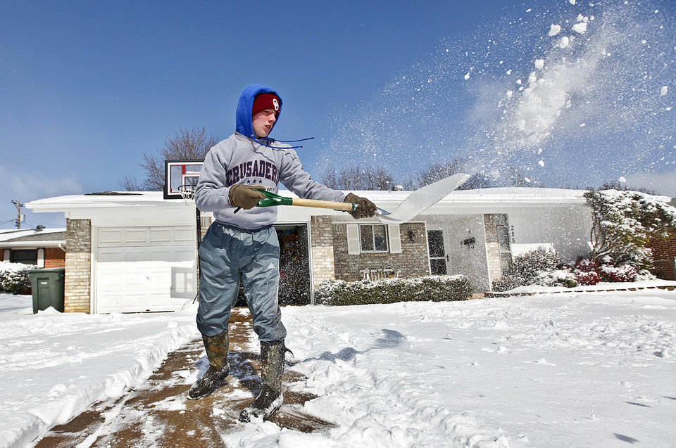Photo - A.J. Ferguson shovel snow as he works to clear his driveway on 30th street on Wednesday, Feb. 9, 2011, Edmond, Okla.  Photo by Chris Landsberger, The Oklahoman