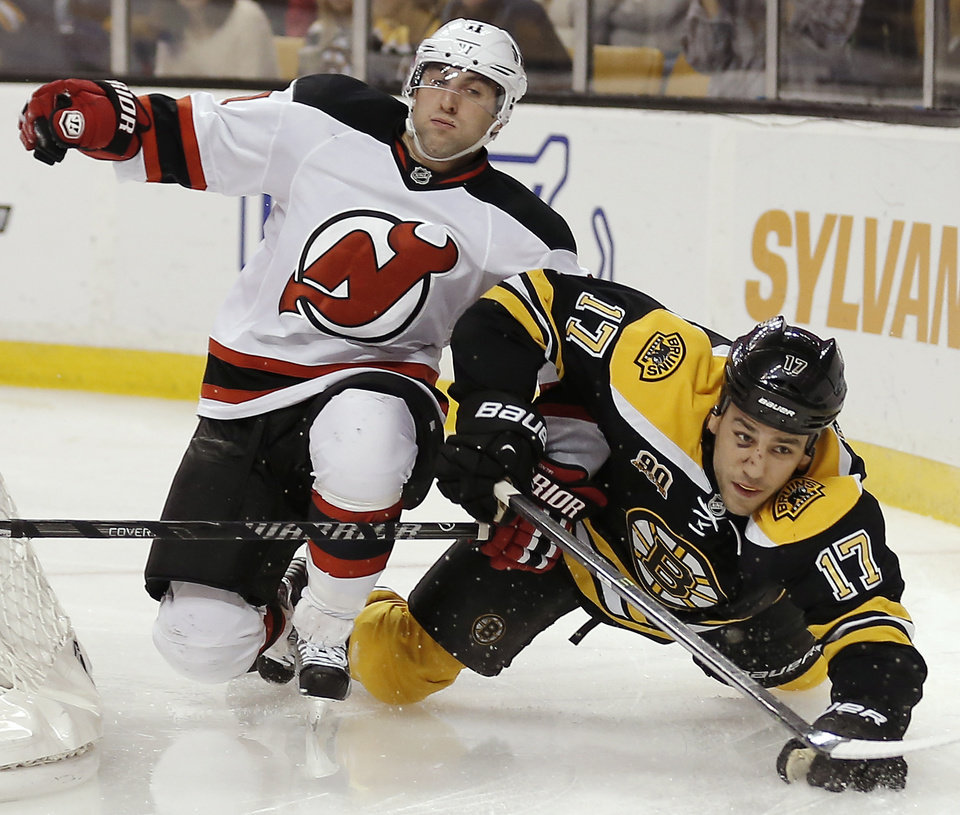 Photo - New Jersey Devils' Stephen Gionta, left, spills Boston Bruins' Milan Lucic (17) during the second period of an NHL hockey game in Boston, Saturday, Oct. 26, 2013. (AP Photo/Winslow Townson)