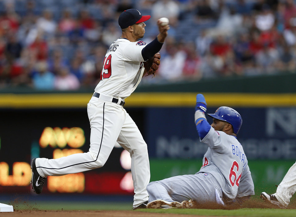 Photo - Atlanta Braves shortstop Andrelton Simmons (19) avoids Chicago Cubs' Emilio Bonifacio (64) as he turns a double play on a Ryan Kalish (51) ground ball in the first inning of a baseball game on Saturday, May 10, 2014, in Atlanta. (AP Photo/John Bazemore)