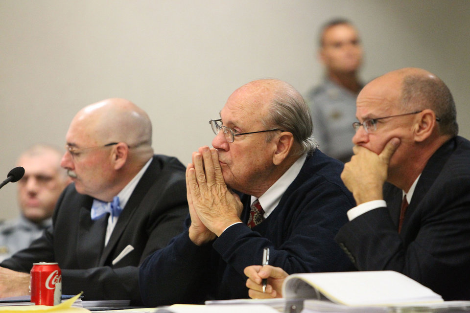 Photo - Former Tampa Police captain Curtis Reeves, Jr., center, sits beside his defense attorneys Richard Escobar, right, and Dino Michaels as they listen to his taped interview by detectives during his bond reduction hearing before Circuit Judge Pat Siracusa at the Robert D. Sumner Judicial Center in Dade City Friday, Feb. 7, 2014. Reeves is suspected of fatally shooting Chad Oulson, 43, and wounding his wife, Nicole, 33, during an argument Jan. 13 over texting at the Cobb Grove 16 theater in Wesley Chapel, Fla.  (AP Photo/Pool Tampa Bay Times, Brendan Fitterer, Pool)