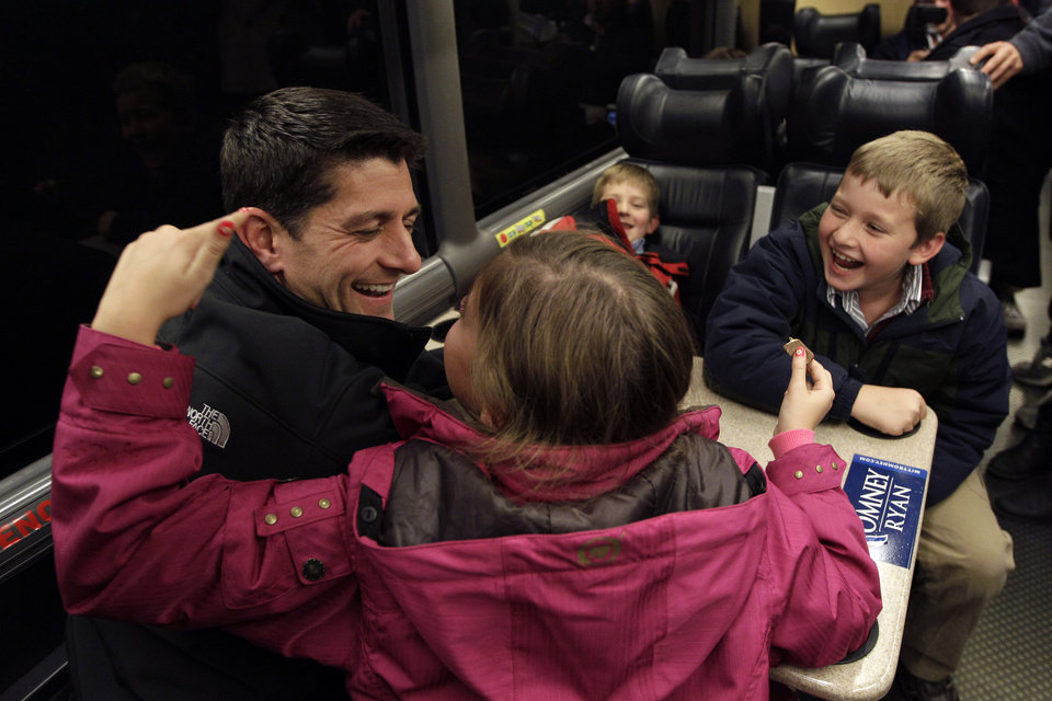 Republican vice presidential candidate, Rep. Paul Ryan, R-Wis., talks to his children, Liza, foreground, Sam, left, and Charlie on the campaign bus on a the way to a rally in Milwaukee, Wis., Monday, Nov. 5, 2012. (AP Photo/Mary Altaffer)