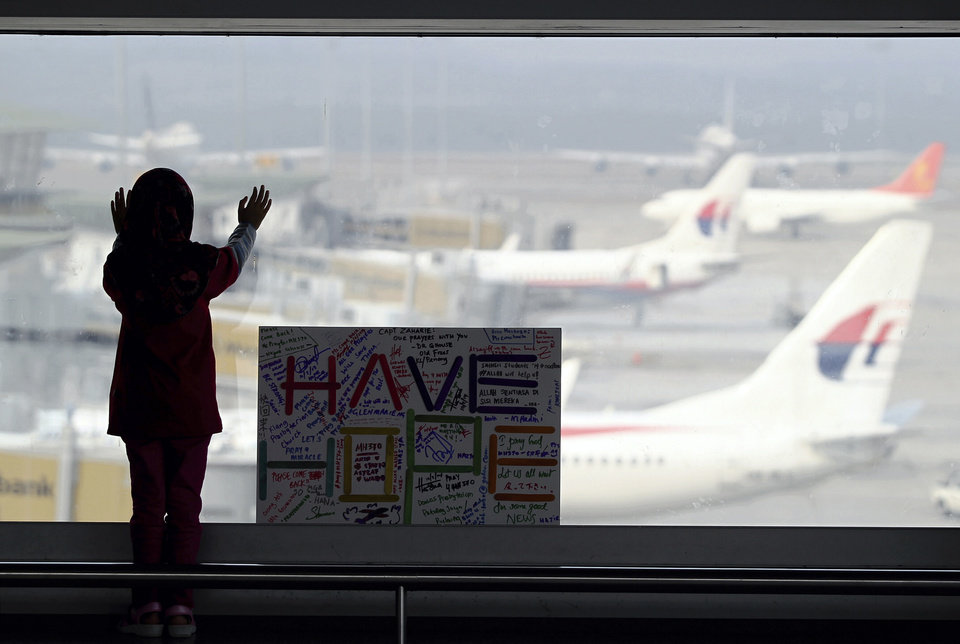 Photo - A girl stands next to a sign board made and written by the public at Kuala Lumpur International Airport in Sepang, Malaysia, Monday, March 10, 2014. Vietnamese aircraft spotted what they suspected was one of the doors of the missing Boeing 777 on Sunday, while questions emerged about how two passengers managed to board the ill-fated aircraft using stolen passports. (AP Photo/Daniel Chan)