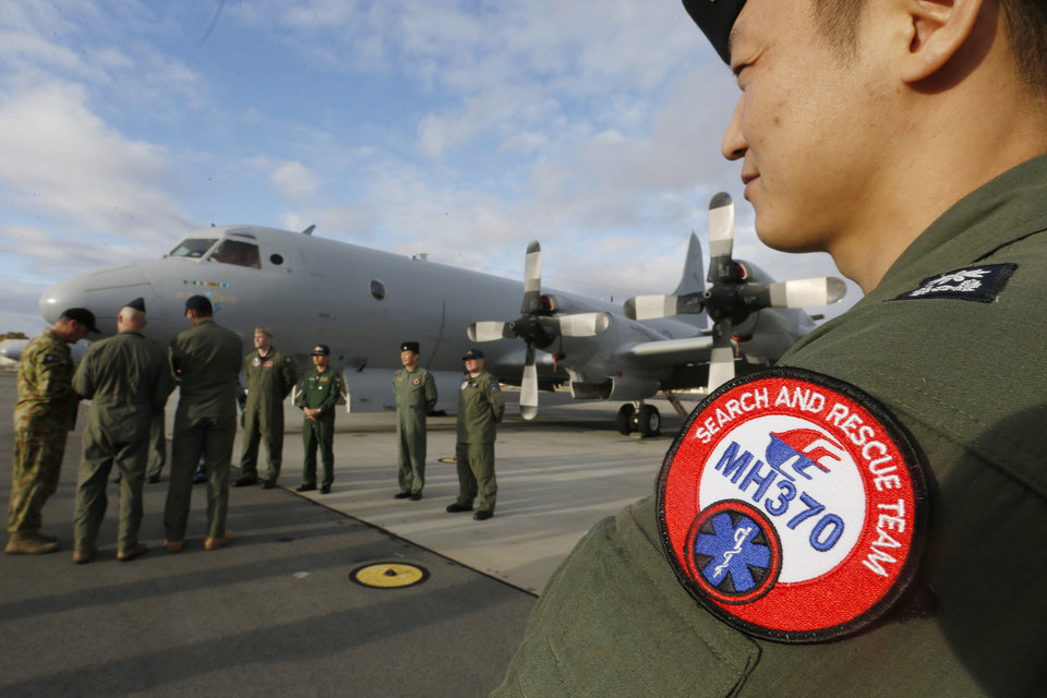 Photo - South Korean Navy Lieutenant Commander Oh Kang-min, right, is pictured wearing a Malaysia Airlines Flight MH370 search and rescue team patch on his sleeve as he waits to meet Australian Prime Minister Tony Abbott in front of a Royal Australian Air Force AP-3C Orion aircraft at RAAF Base Pearce near Perth Monday, March 31, 2014. Abbott met with members of various international military forces currently searching for the missing plane in the Indian Ocean on Monday. (AP Photo/Jason Reed, Pool)