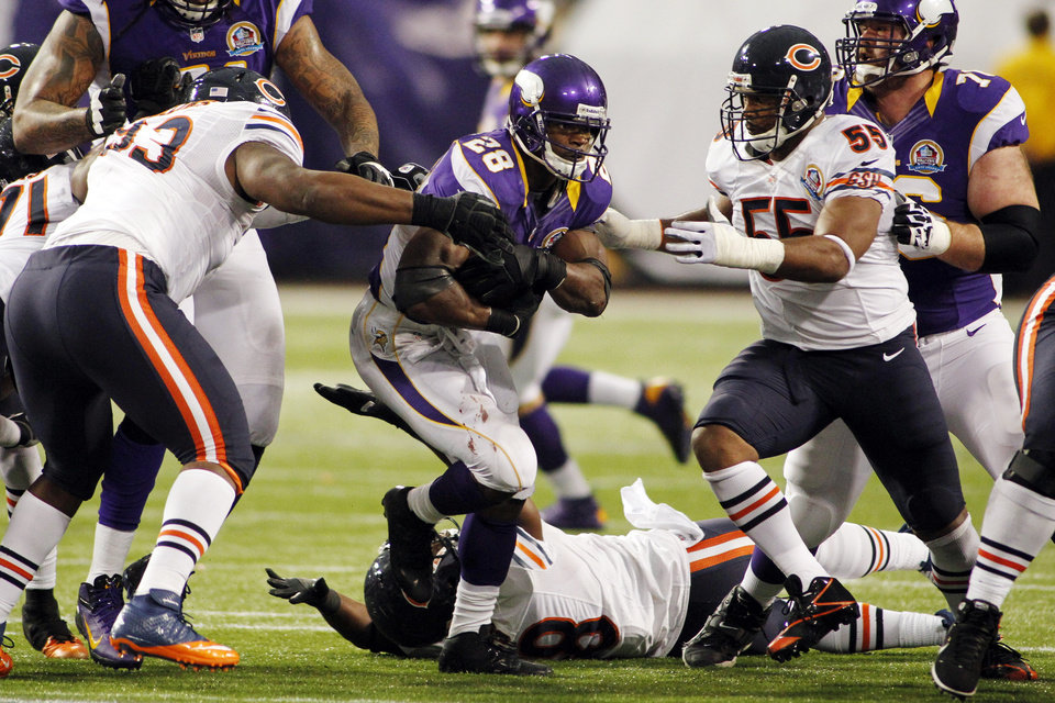 Minnesota Vikings running back Adrian Peterson (28) rushes between Chicago Bears' Nate Collins, left, and Lance Briggs, right, during the second half of an NFL football game, Sunday, Dec. 9, 2012, in Minneapolis. The Vikings won 21-14. (AP Photo/Andy King)